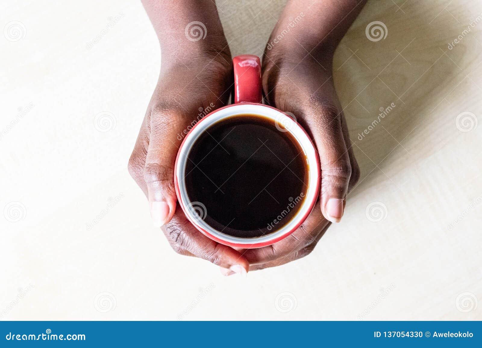 Афро-американские женские руки держа красные эспрессо или капучино чашки кофе дальше на рабочей поверхности кухни гранита Рука че