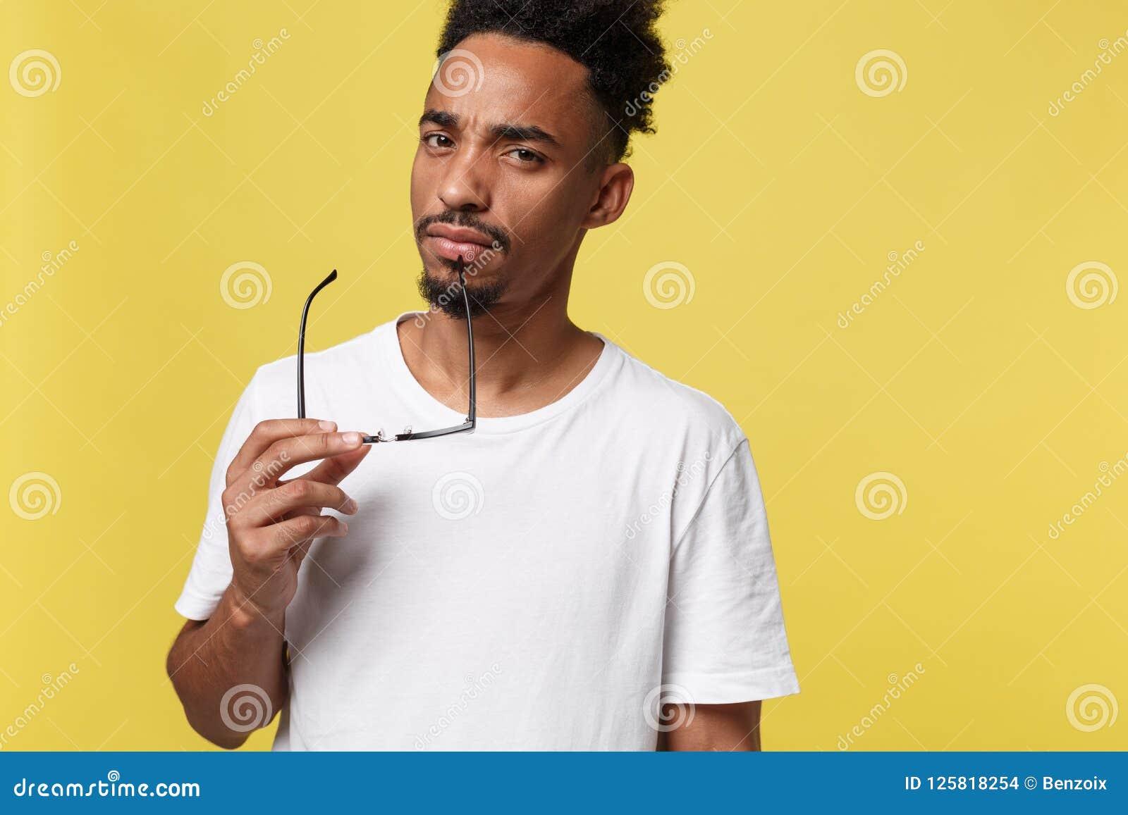 Афро-американский бизнесмен держа стекло, изолированное на желтой предпосылке - чернокожие люди