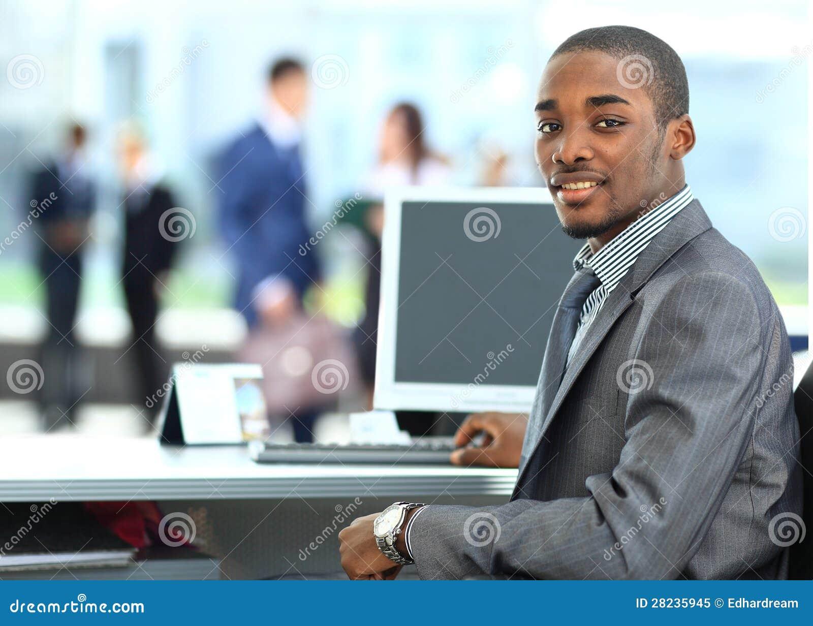 Афро-американский предприниматель показывая компьтер-книжку компьютера в офисе