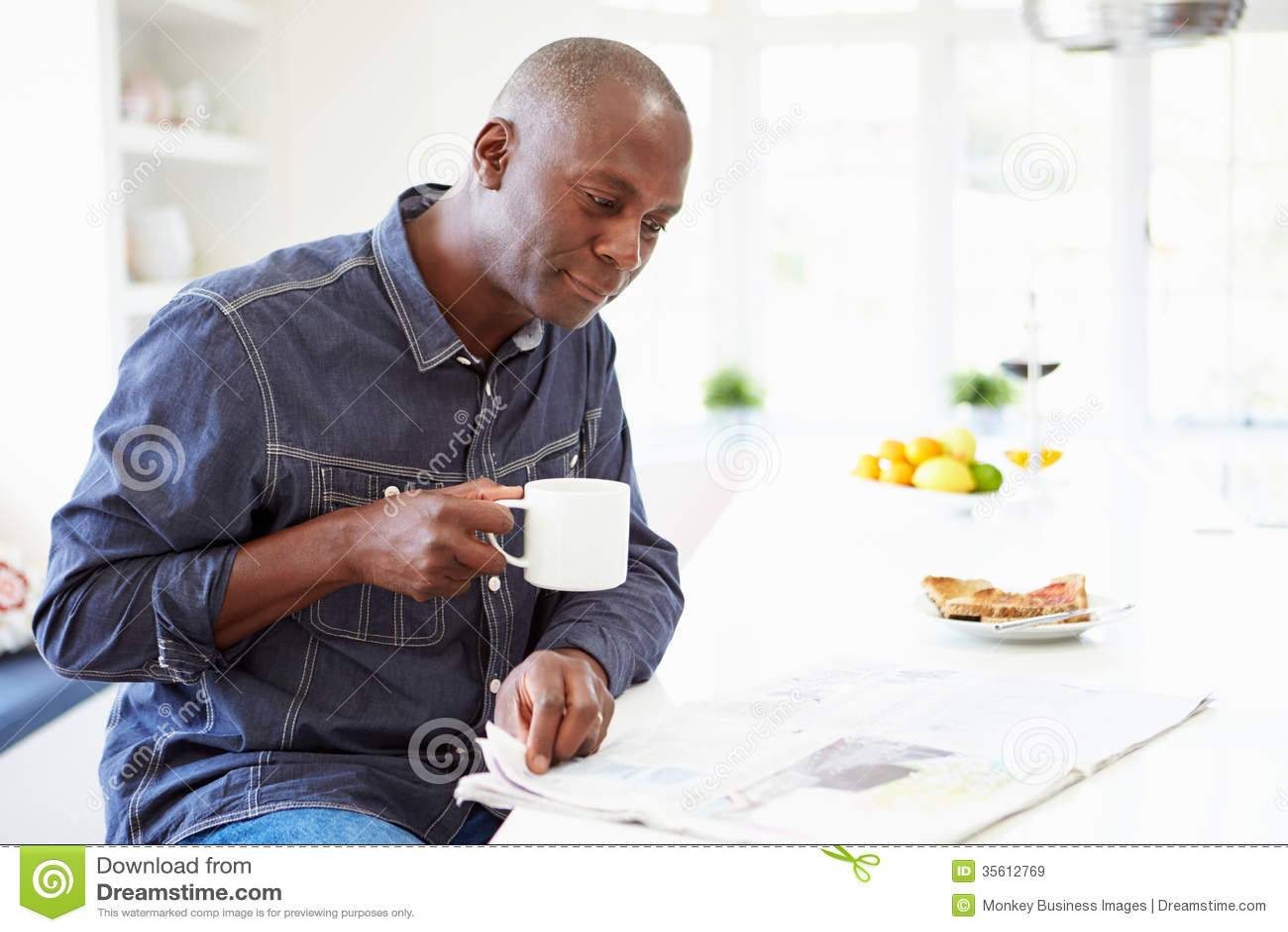 Афро-американский человек есть завтрак и читая газету