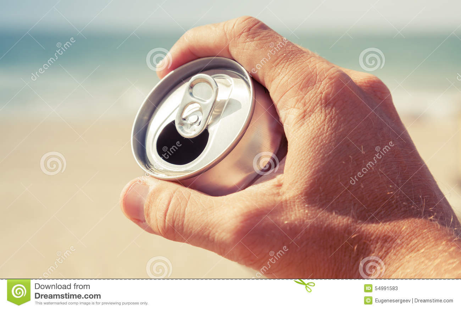 Алюминиевая чонсервная банка пива в мужской руке, тонизированном ретро