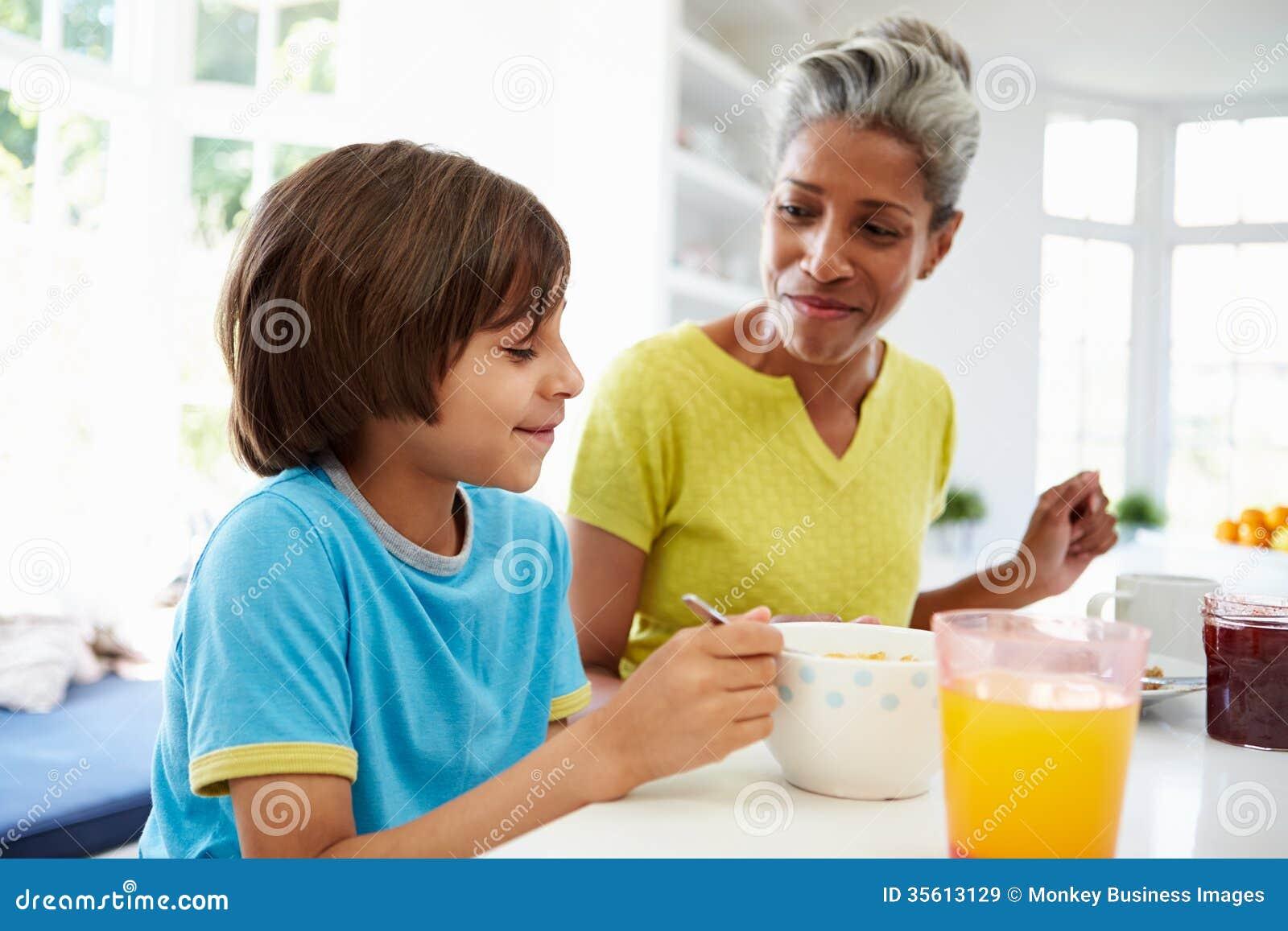 Бабушка и внук имея завтрак совместно