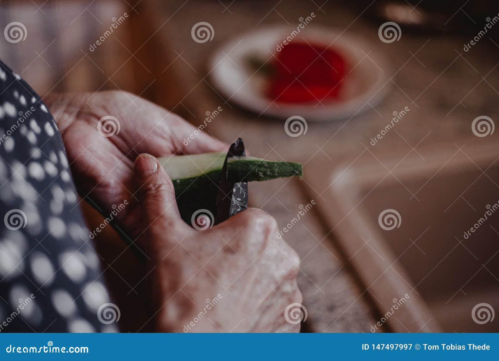 Бабушка режа здоровые овощи в кухне