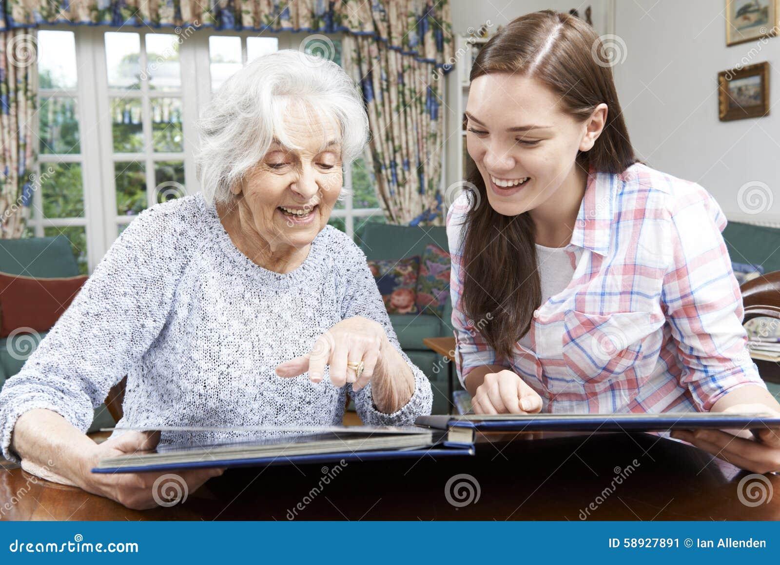 Бабушка смотря фотоальбом с подростковой внучкой