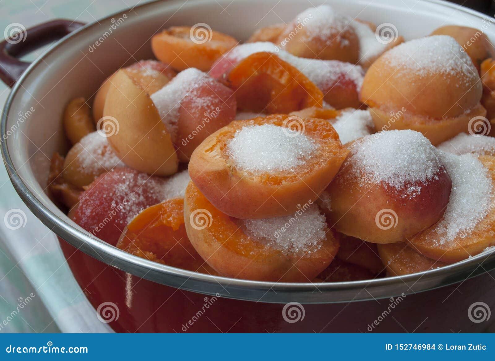 Бак с абрикосами и сахаром готовыми быть сваренным для того чтобы сделать варенье
