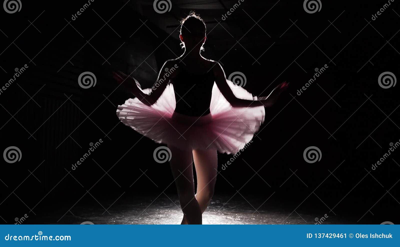 Балерина выполняет повороты fouette в фаре на черной предпосылке в тренируя комнате Балетная пачка женского артиста балета нося сток-видео