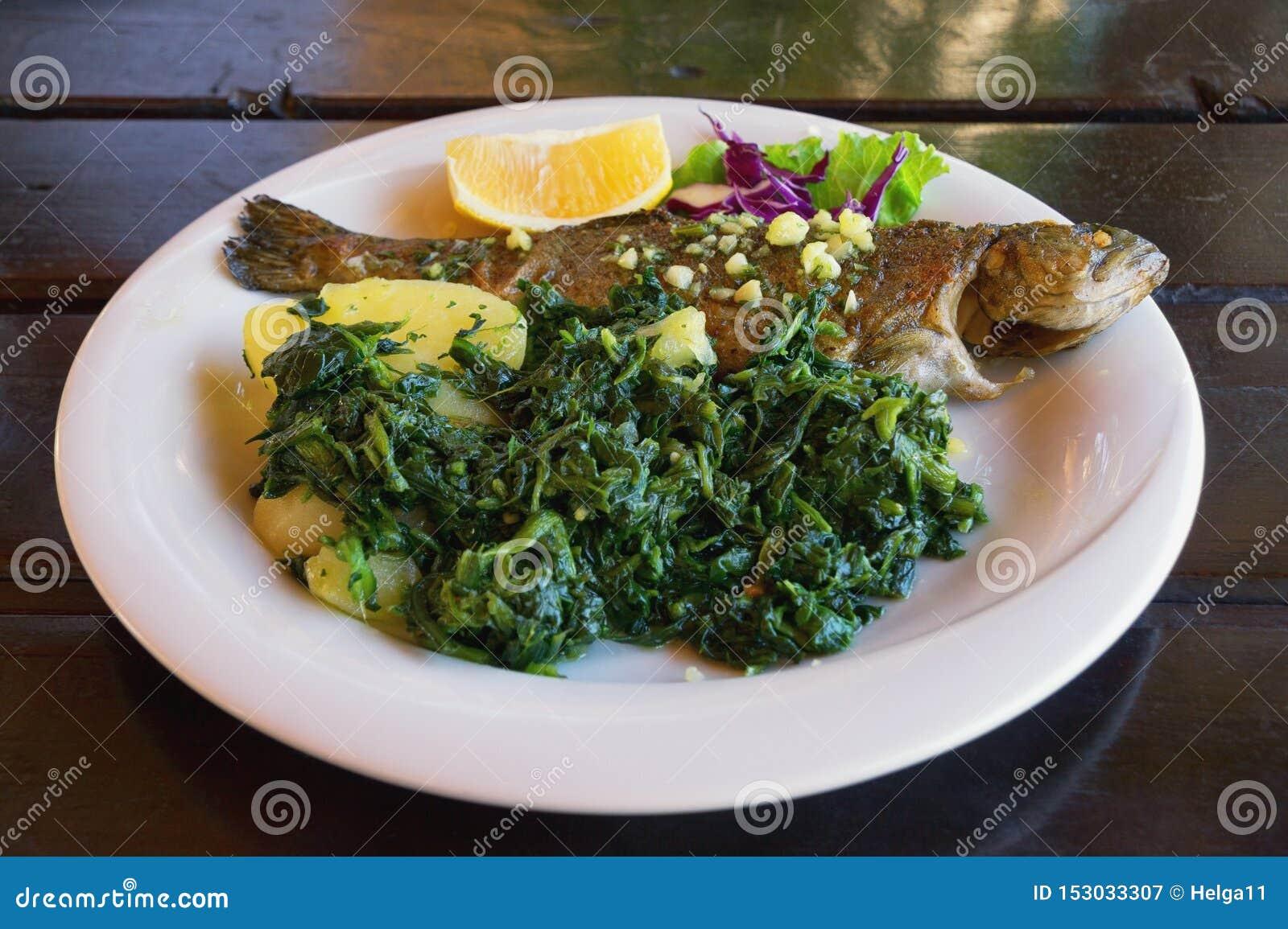 Балканская кухня Зажаренная форель рыб с густолиственными зелеными овощами на белой плите