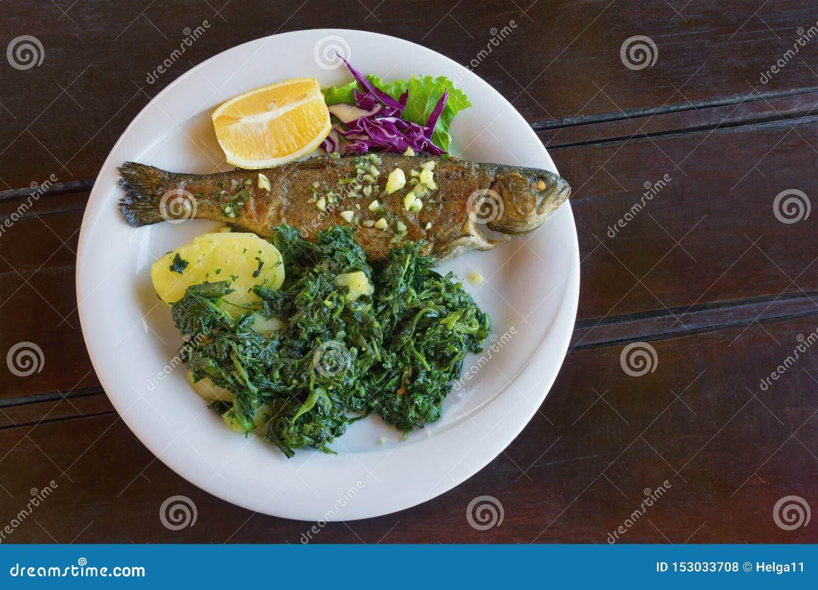 Балканская кухня Зажаренные рыбы с густолиственными зелеными овощами на белой плите Темная деревенская предпосылка Плоское положе