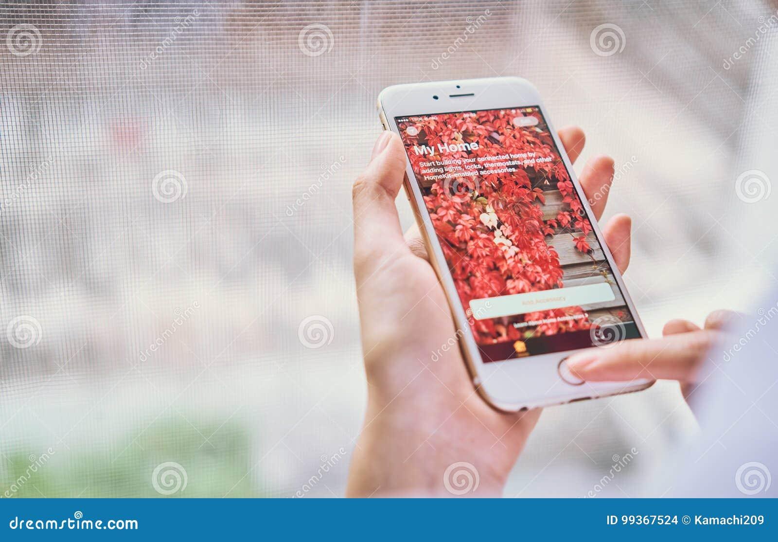 Бангкок, Таиланд - 6-ое сентября 2017: рука отжимает мой дом app для Iphone на ios 10 Новый дом app позволяет вам повернуть дальш