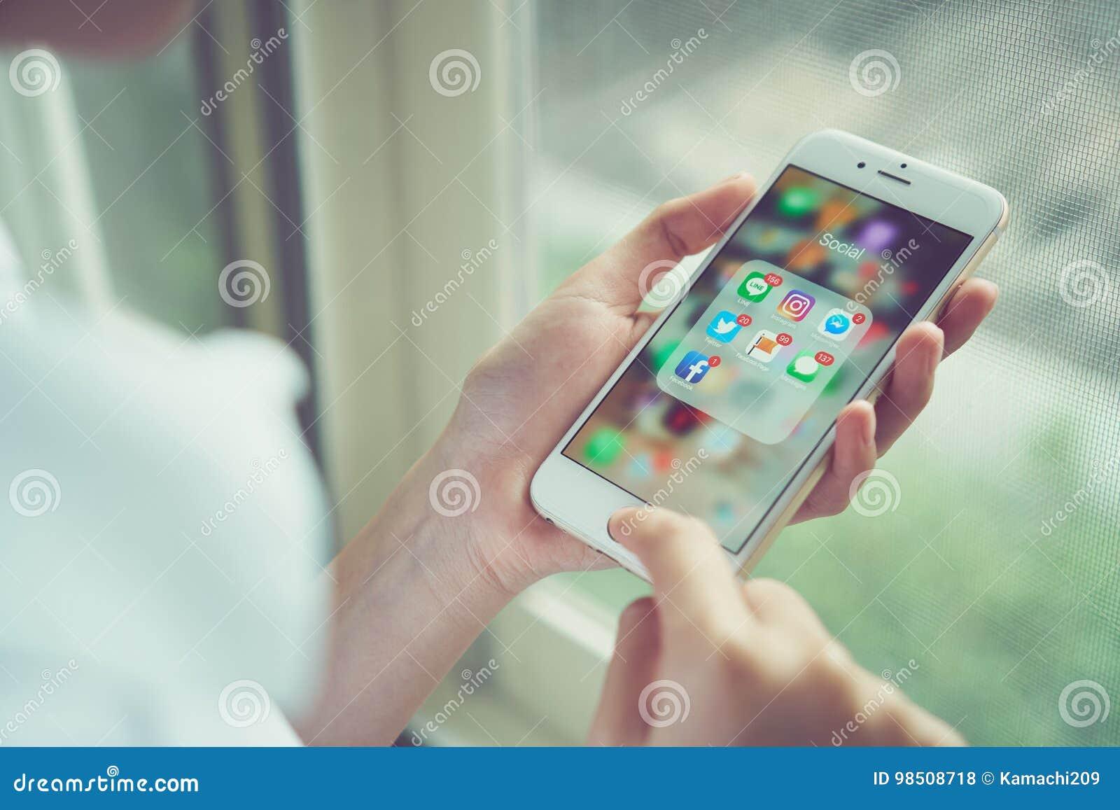 Бангкок, Таиланд - 23-ье августа 2017: женщина используя iPhone экрана средств массовой информации app дисплея выставки социально