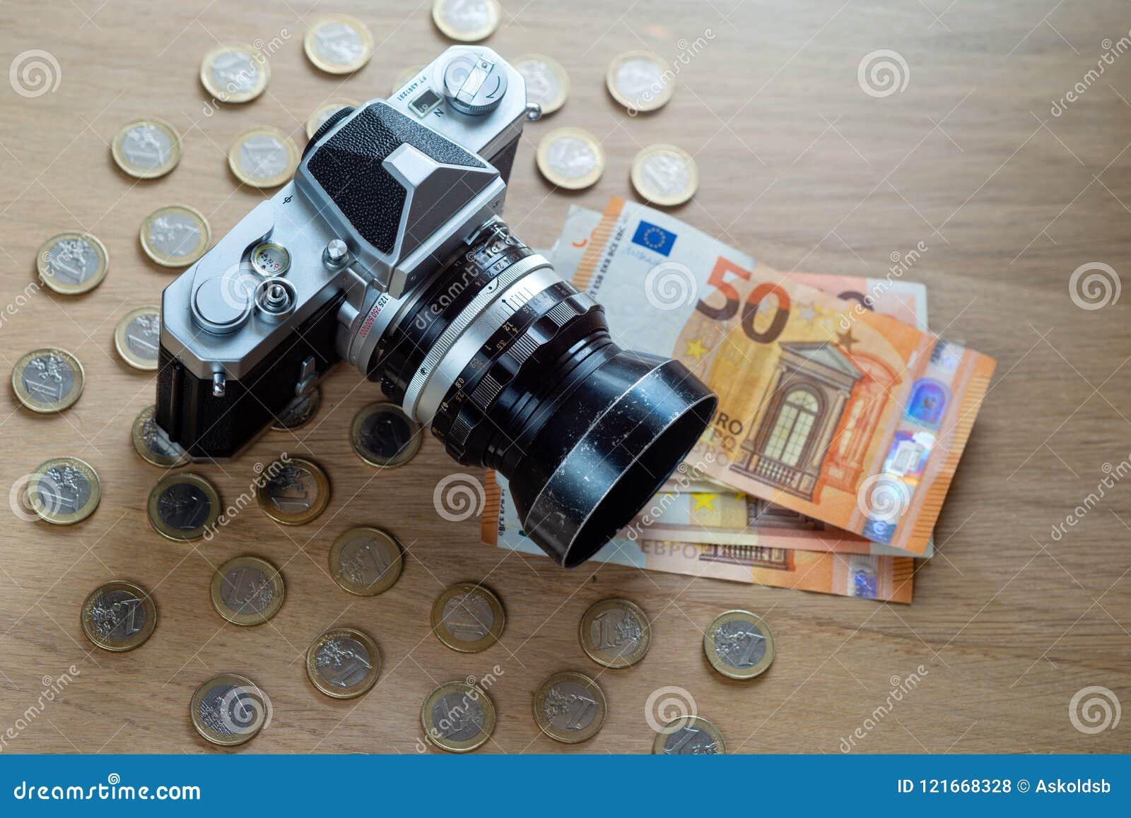 Банкноты евро, монетки и камера на светлой деревянной предпосылке
