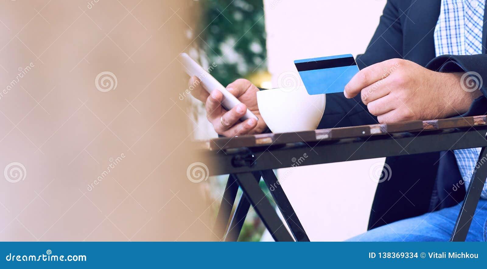 Банк интернета, электронная коммерция и онлайн торгуя концепция Подрезанный взгляд рук бизнесмена держа мобильный телефон и