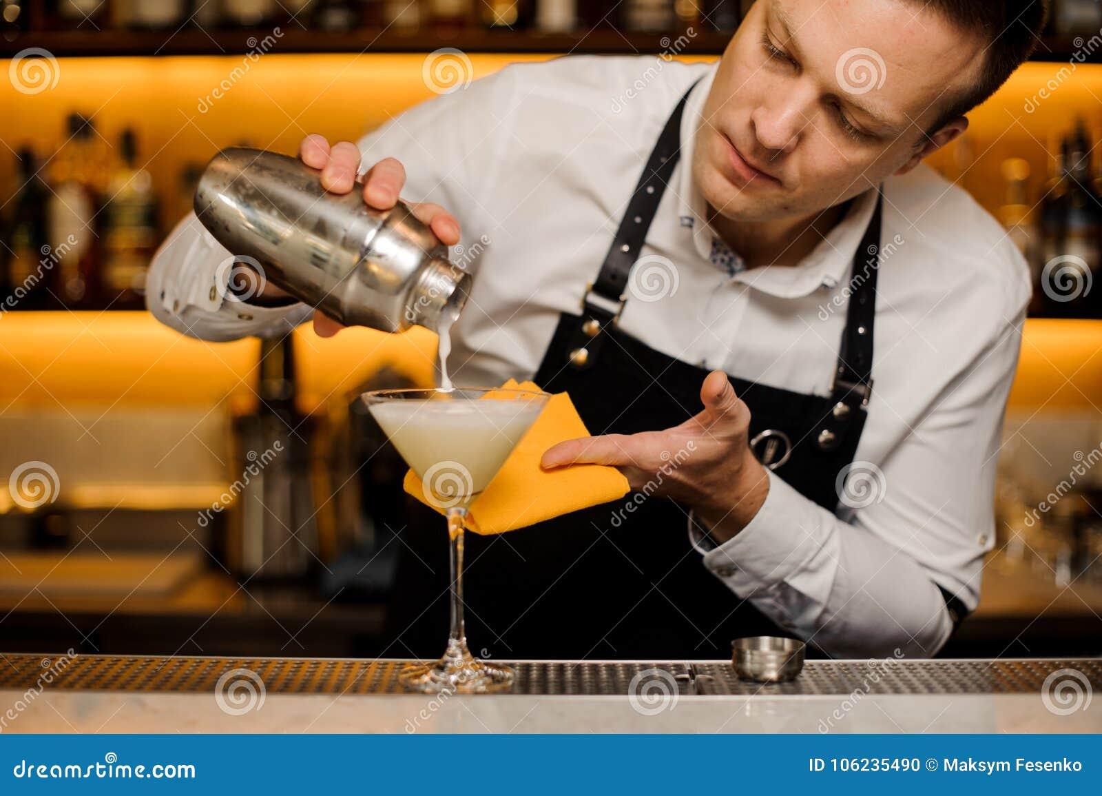 Бармен лить свежий алкогольный напиток в стекло коктеиля