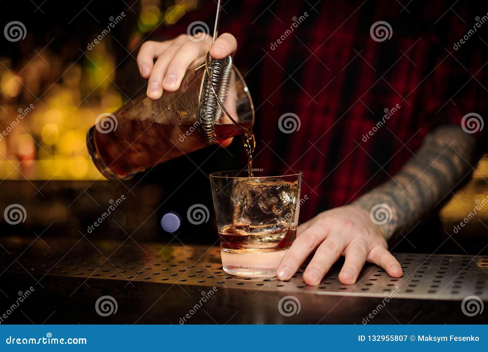 Бармен лить свежий сильный коктейль вискиа в стекло