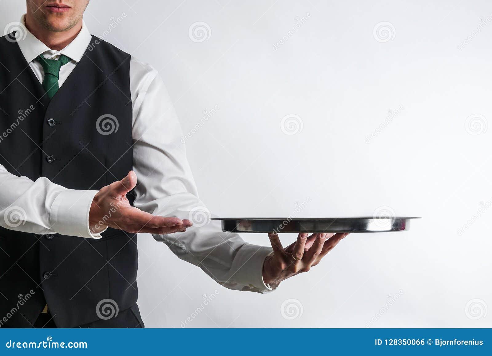 Батлер/кельнер в жилете костюма нося пустой серебряный поднос