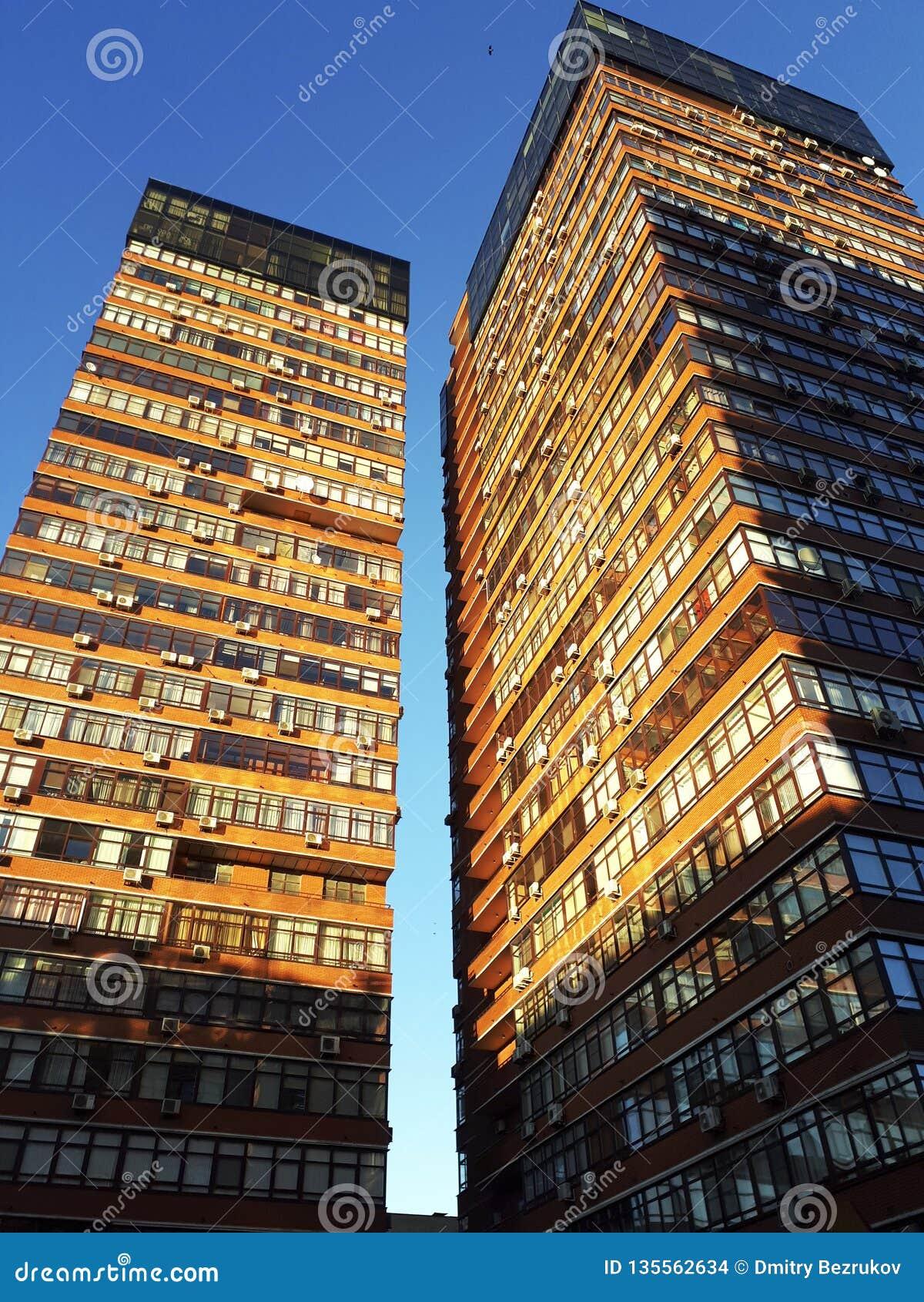 2 башни жилого дома снизу против неба