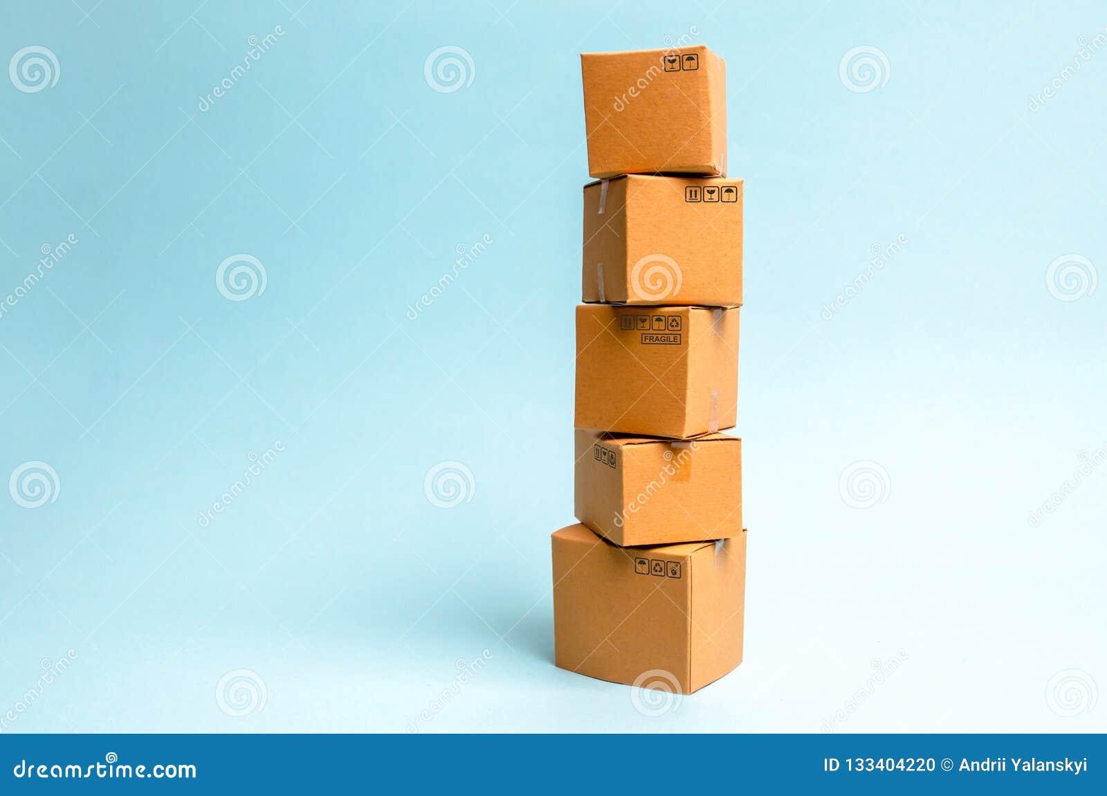 Башня картонных коробок на голубой предпосылке Концепция двигать и доставки товаров и товаров Коммерция и дело