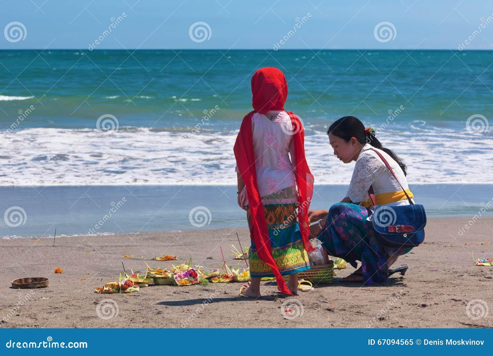 Балийская женщина с ребенком на пляже океана