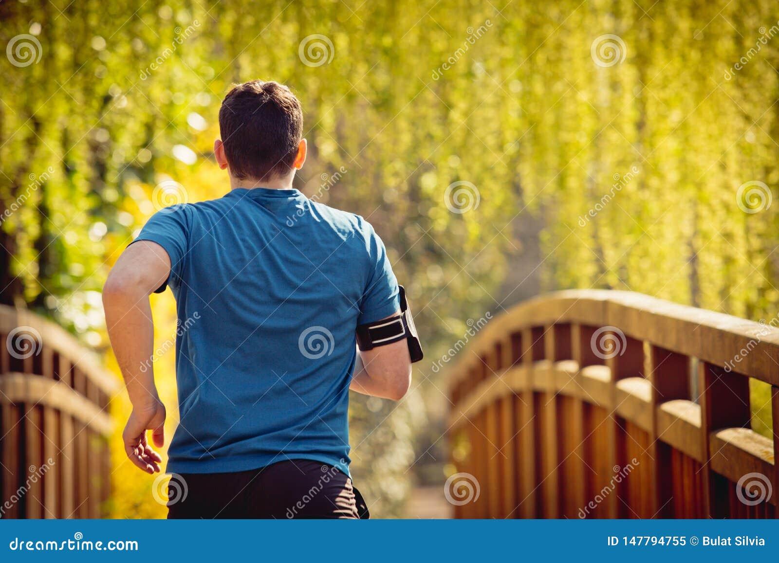 Бегун вида сзади мужской бежать в парке города за мостом