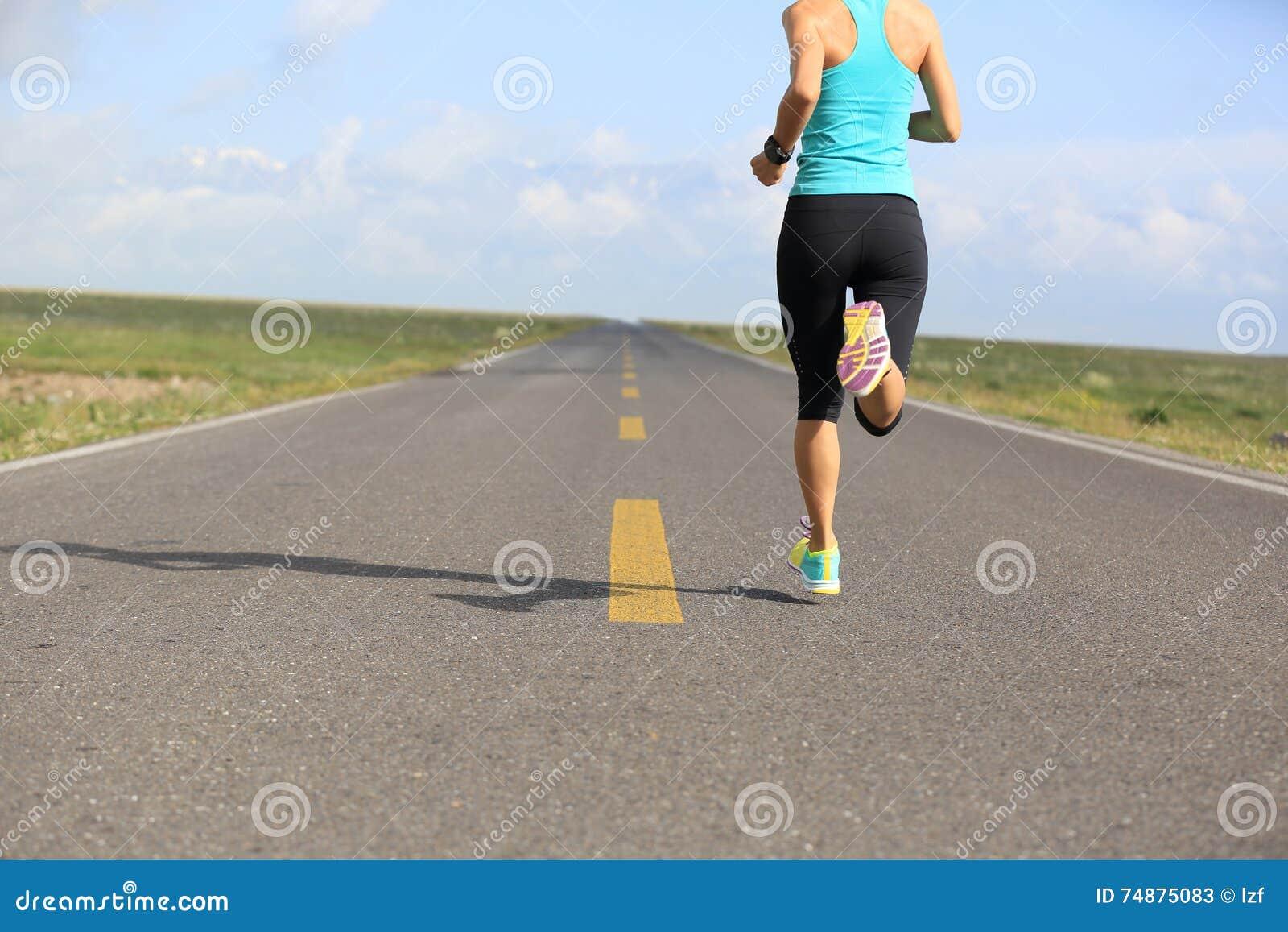 Бегун женщины бежать на дороге