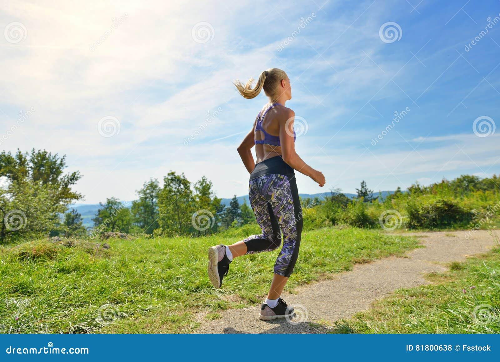 Бегун маленькой девочки jogging на горной тропе в красивом ландшафте