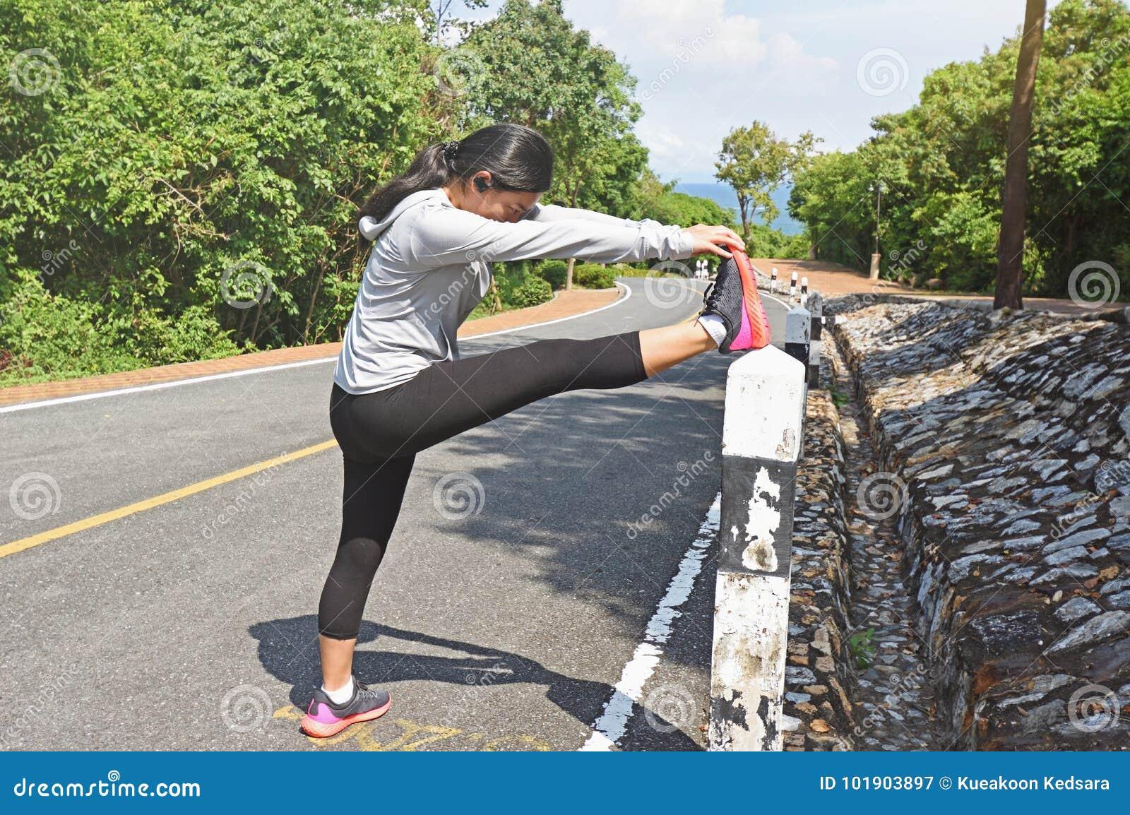 Бегун молодой женщины протягивая ноги перед бежать внешний
