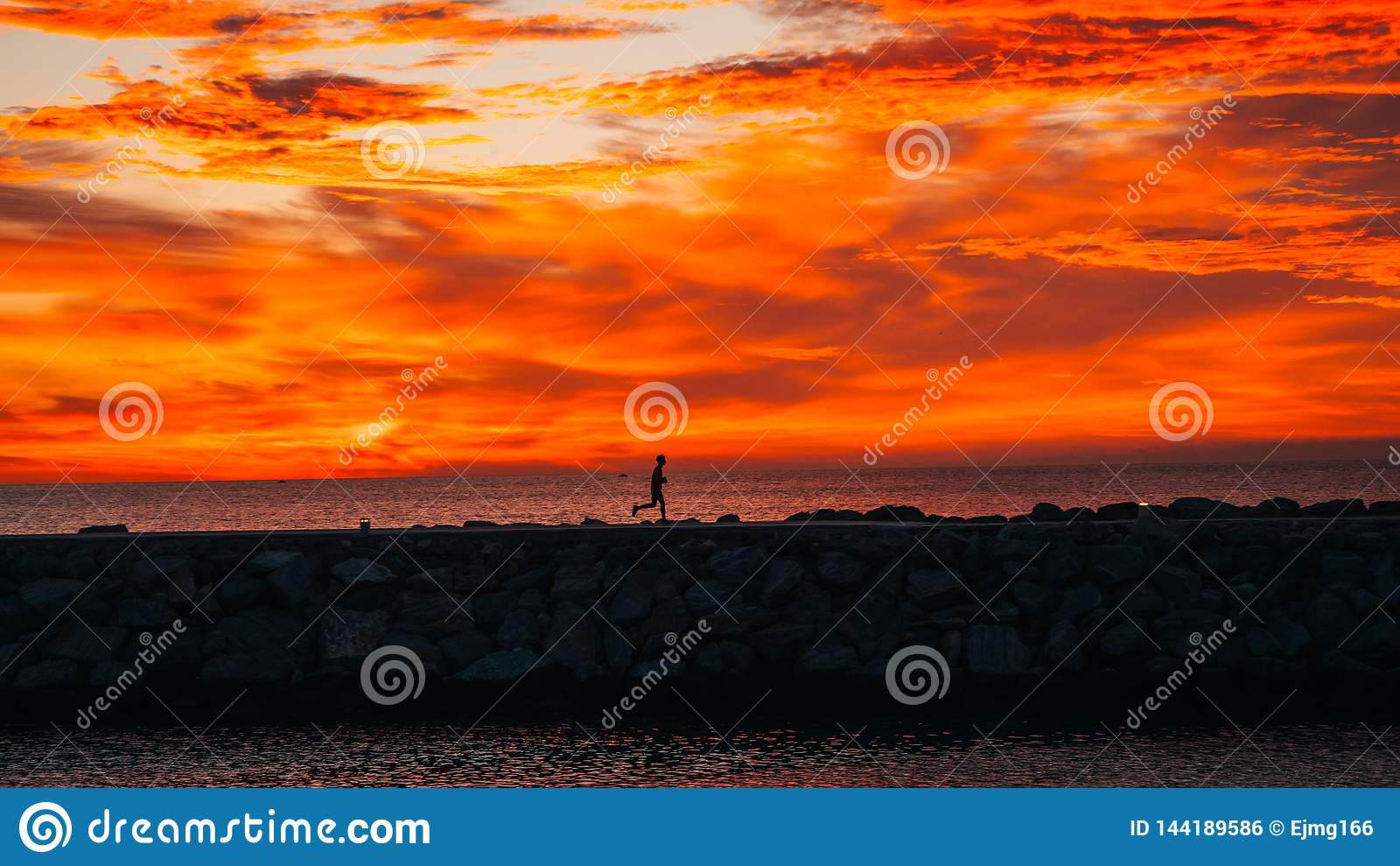 Бегун на восходе солнца бежать рядом с морем