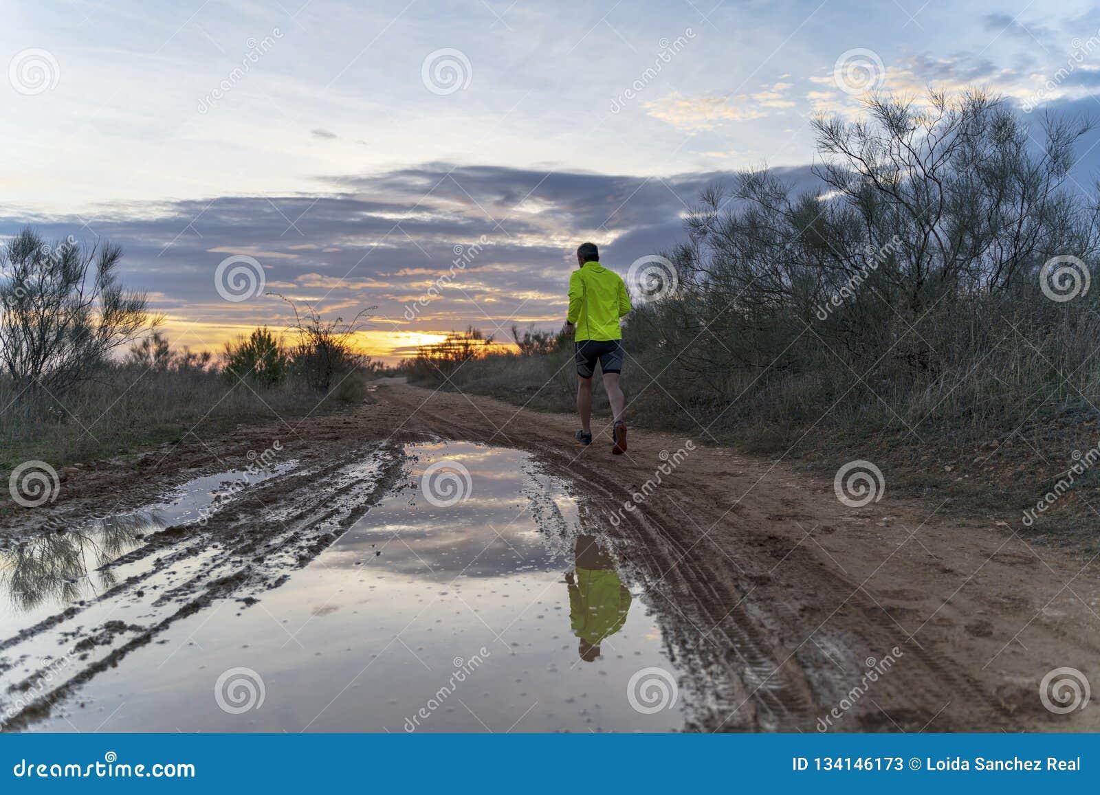Бегущ в поле на заходе солнца в шортах, с тапками