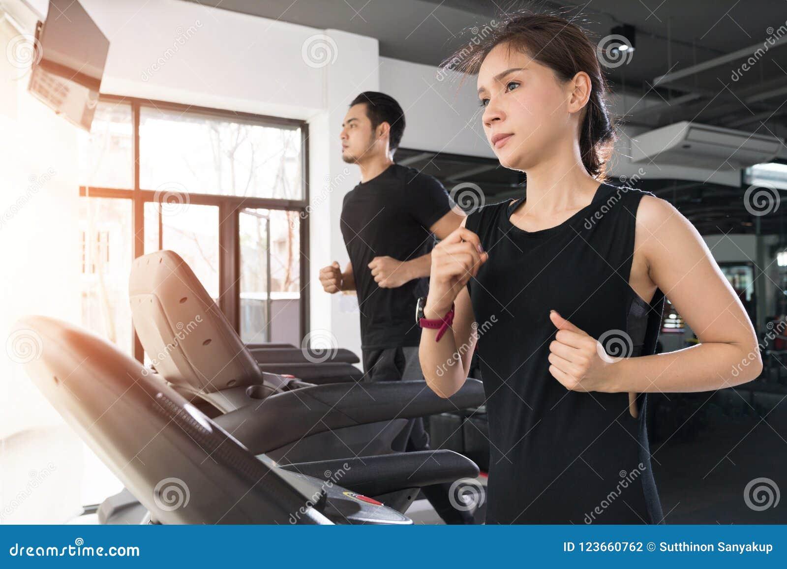 Бегущ на третбанах, активной молодой женщине и человеке бежать на третбане в спортзале