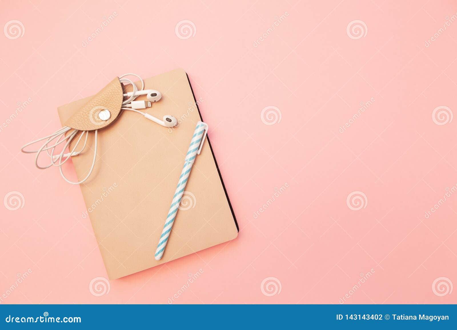 Бежевый дневник с голубой ручкой и наушники на пастельной тысячелетней розовой бумажной предпосылке Концепция образования, ведя б