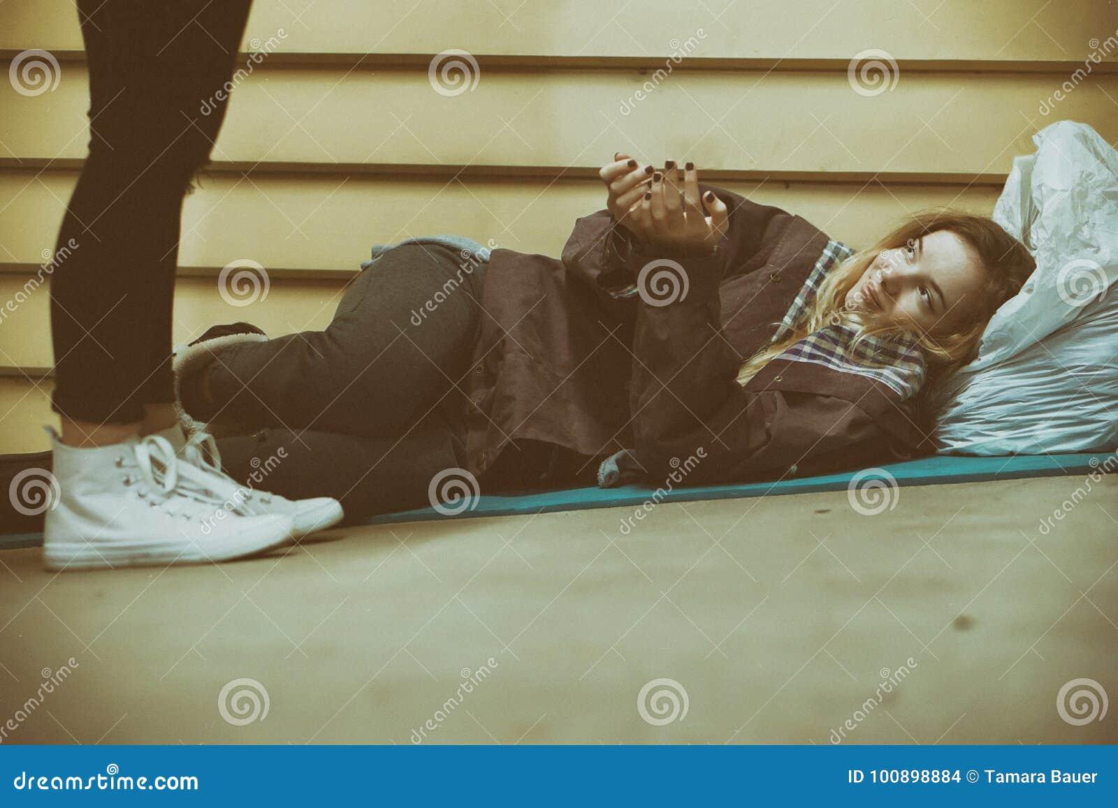 Бездомный подросток получая помощь незнакомцем