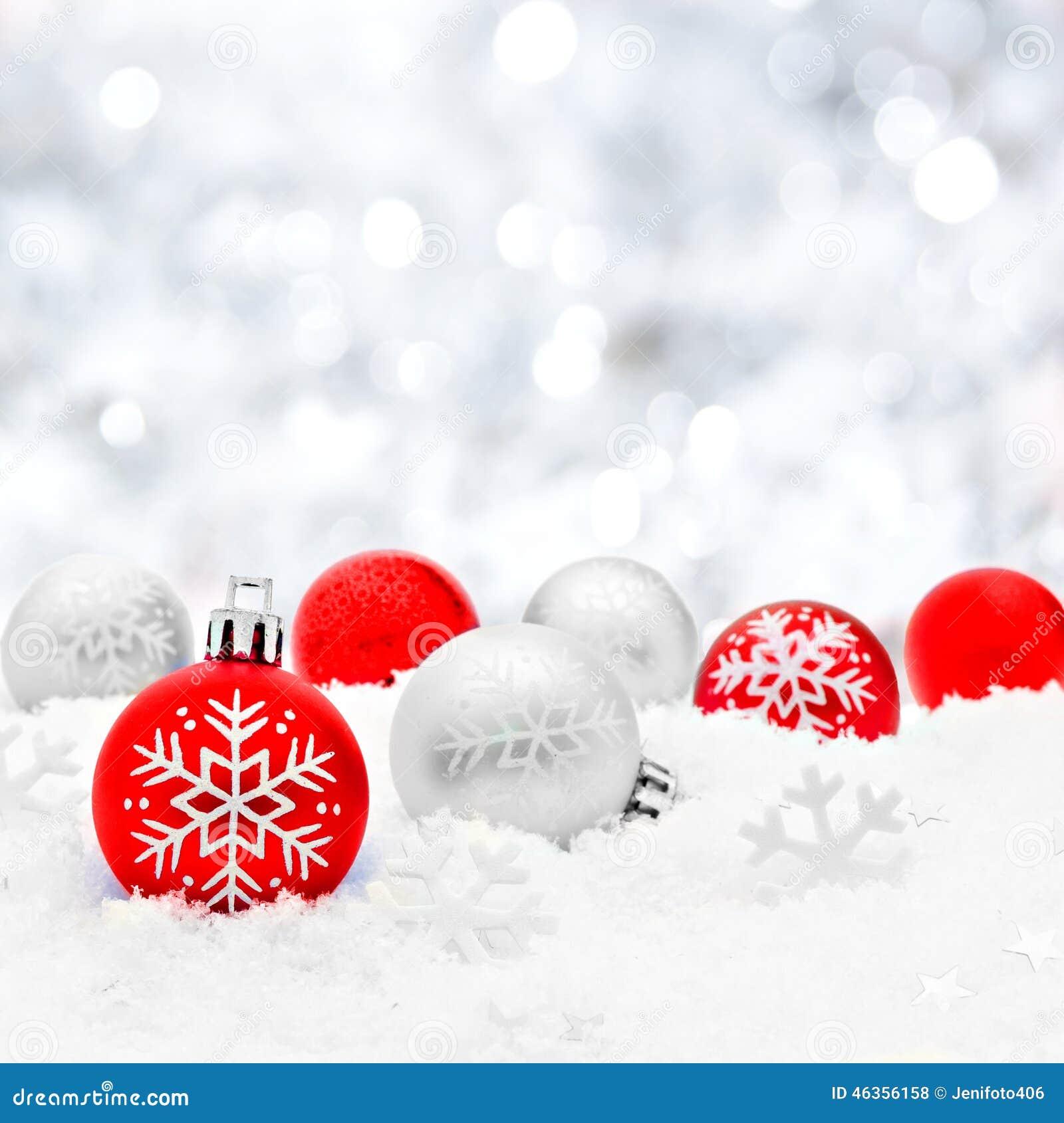 Безделушки рождества в снеге с серебряной предпосылкой