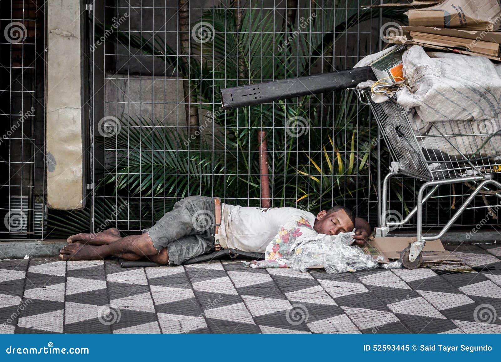 Бездомный человек спит с магазинной тележкаой