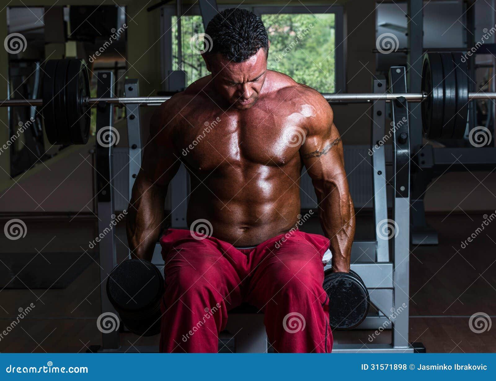 Без рубашки культурист делая тяжеловесную тренировку для бицепса