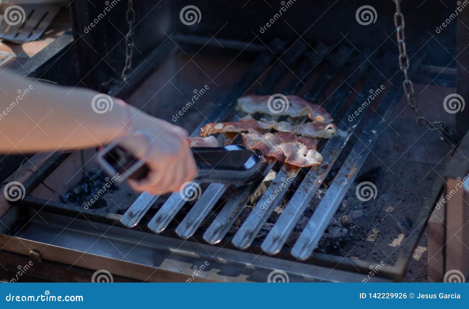 Бекон варя на барбекю угля с руками держа пару схватов