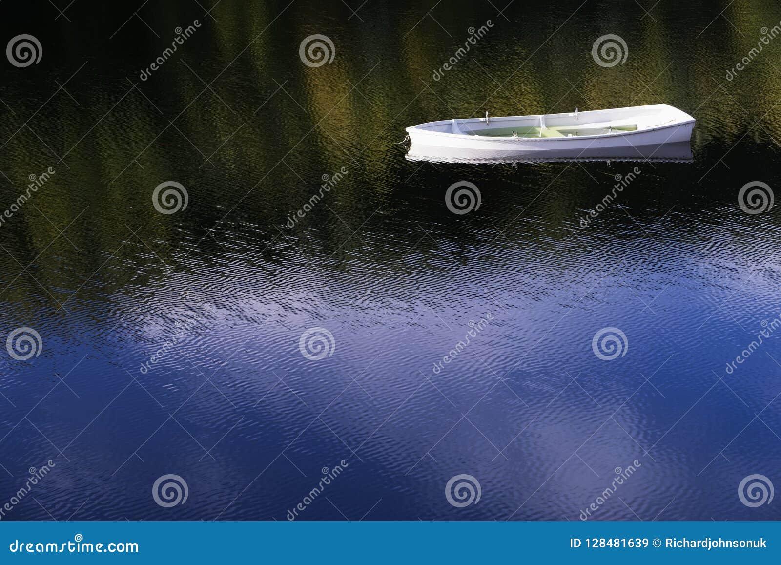 Белая ангеликовая одиночная сиротливая шлюпка плавая мирный mindfulness неги в спокойной воде при солнце отражения голубого неба