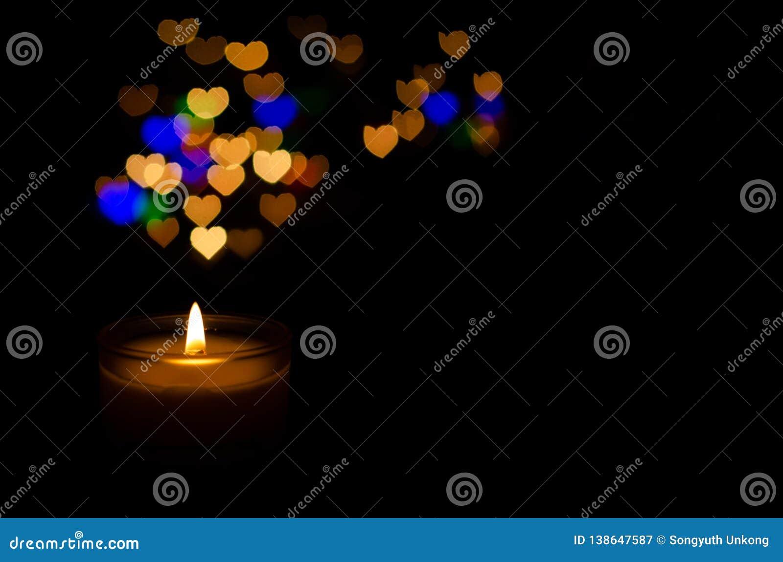Белая ароматичная стеклянная свеча с пламенем и красочным bokeh формы любов
