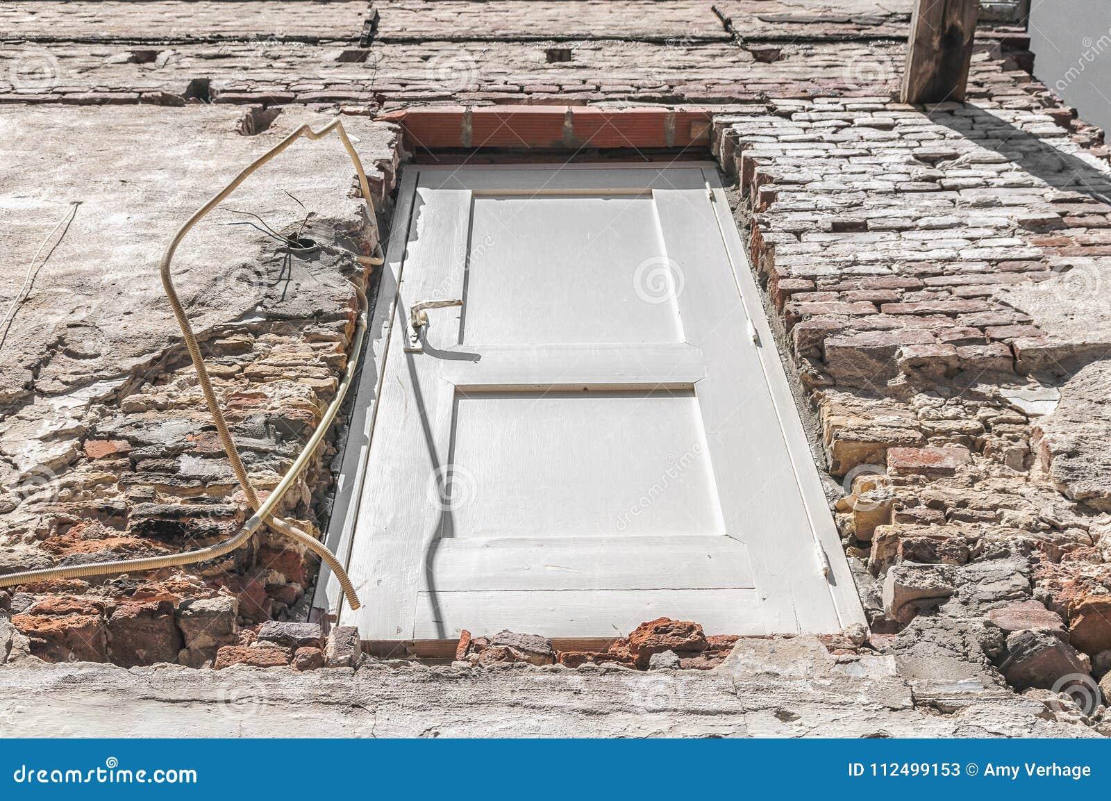 Белая деревянная дверь видимая в каменной стене