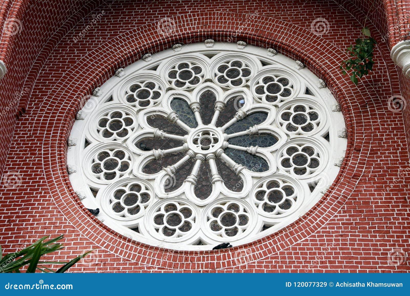 Белая картина цветка миномета круга с цветным стеклом и красным кирпичом экстерьера щипца церков на соборе святой троицы