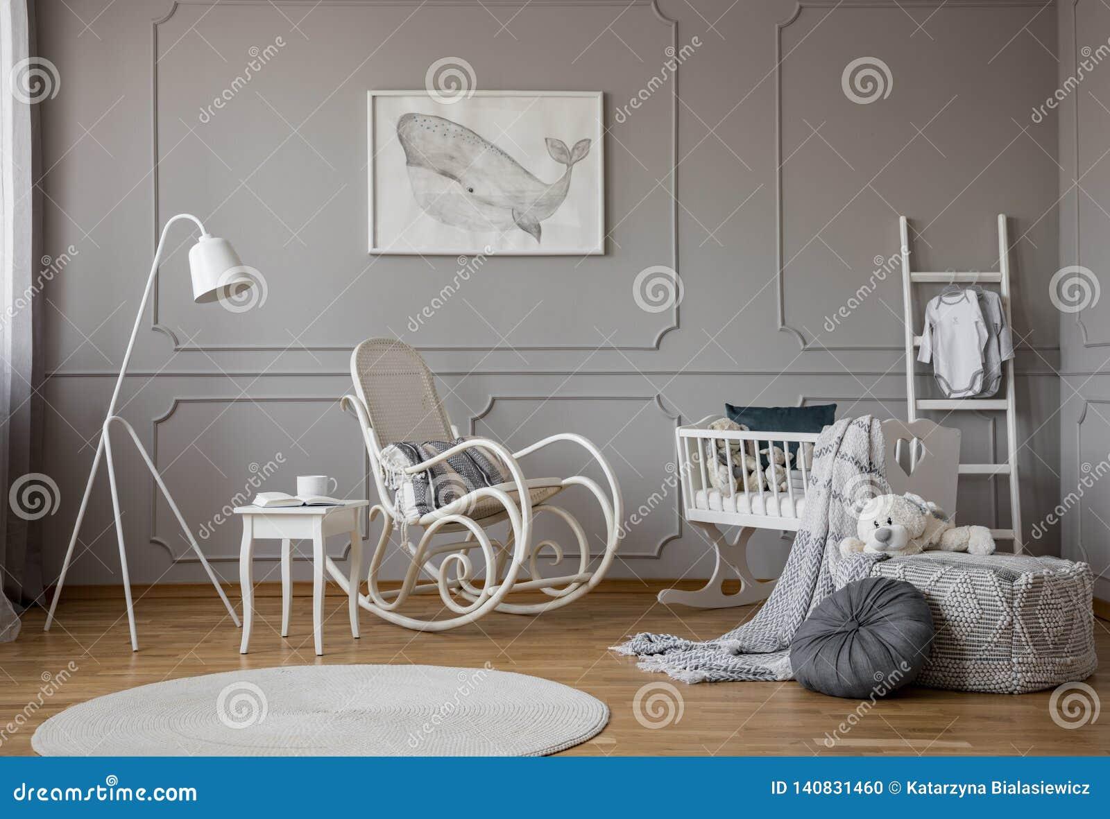 Белая кресло-качалка с подушкой в середине уютного интерьера комнаты младенца с деревянным вашгердом, промышленной белой лампой и