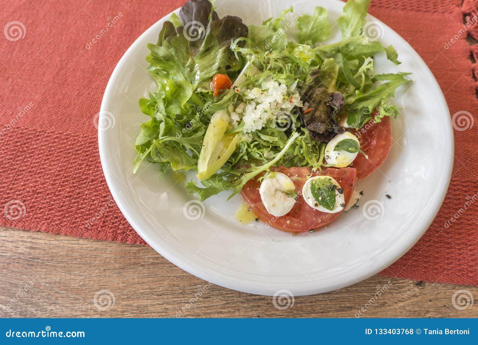 Белая плита с салатом, томатами, моццареллой и базиликом