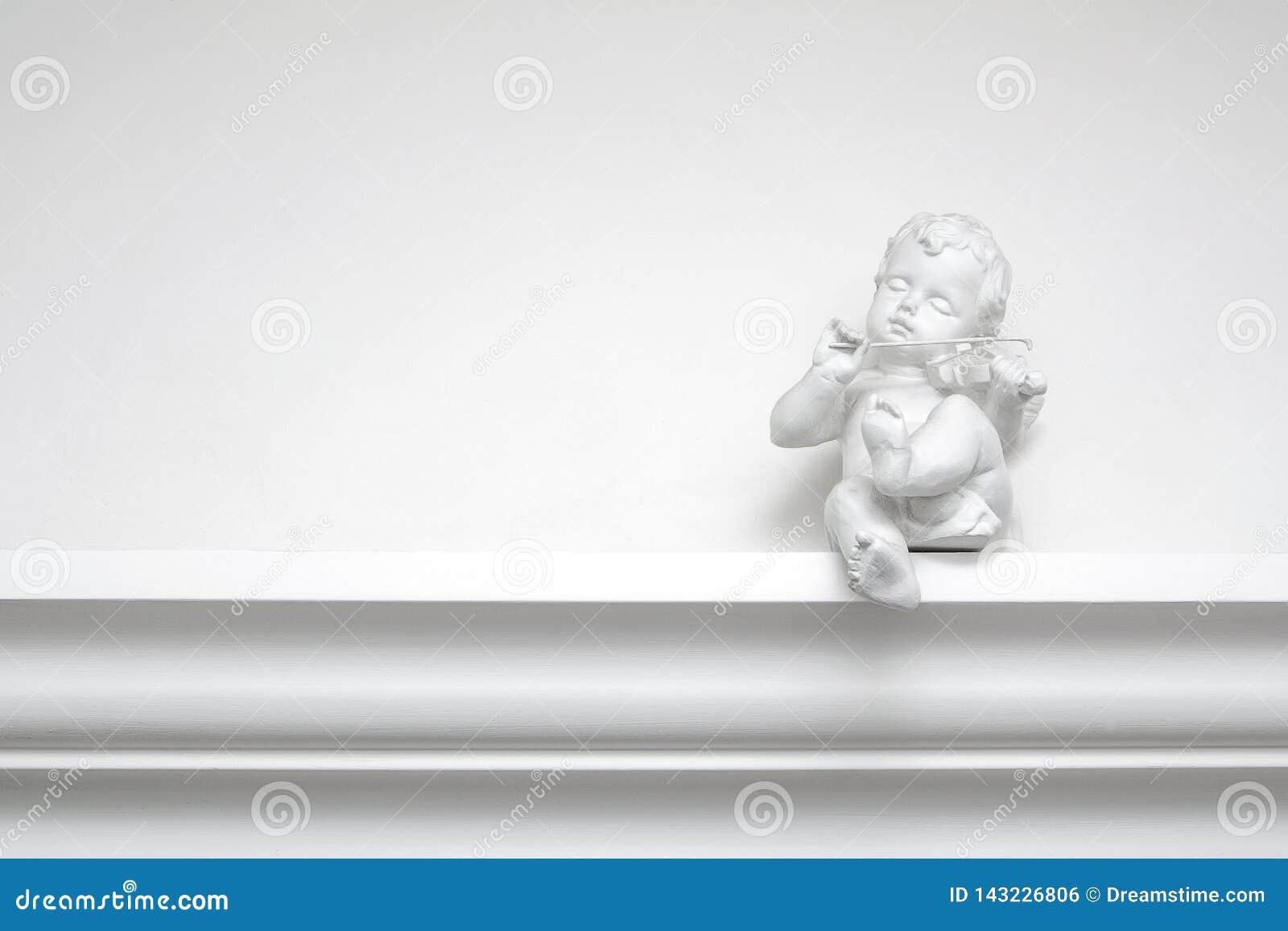Белая скульптура ангела гипсолита со скрипкой