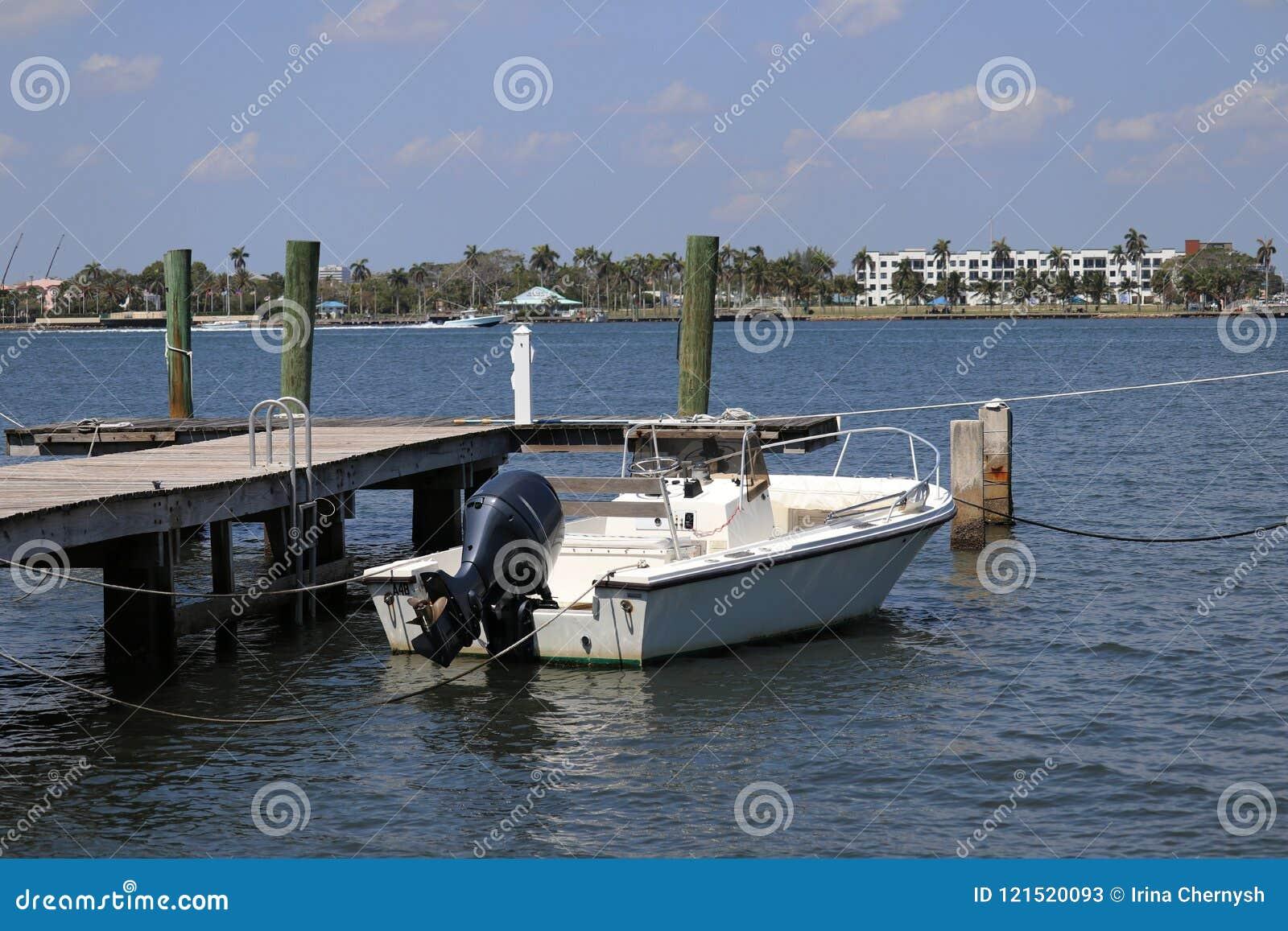 Белая шлюпка около частной пристани в Флориде в голубом море с голубым небом
