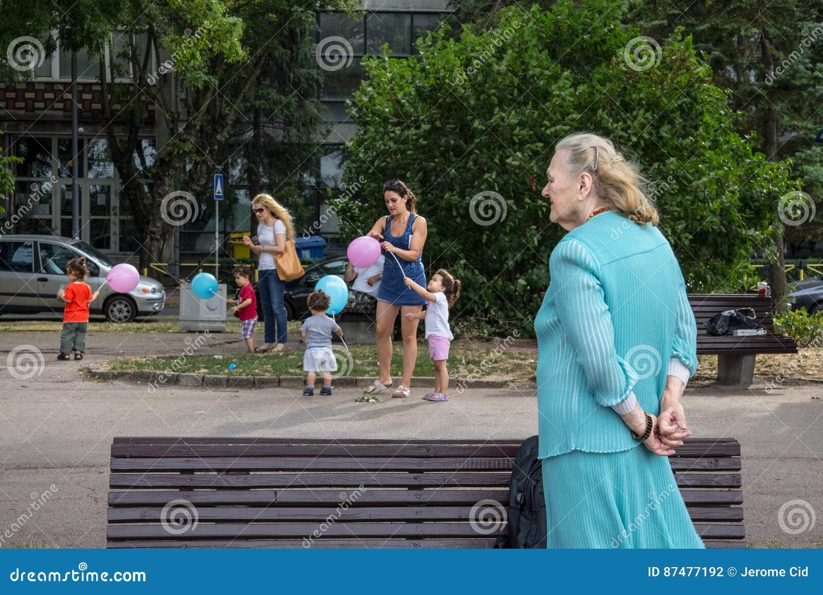 БЕЛГРАД, СЕРБИЯ - 2-ОЕ АВГУСТА 2015: Старуха смотря более молодых женщин позаботить о дети играя с воздушными шарами в пригороде