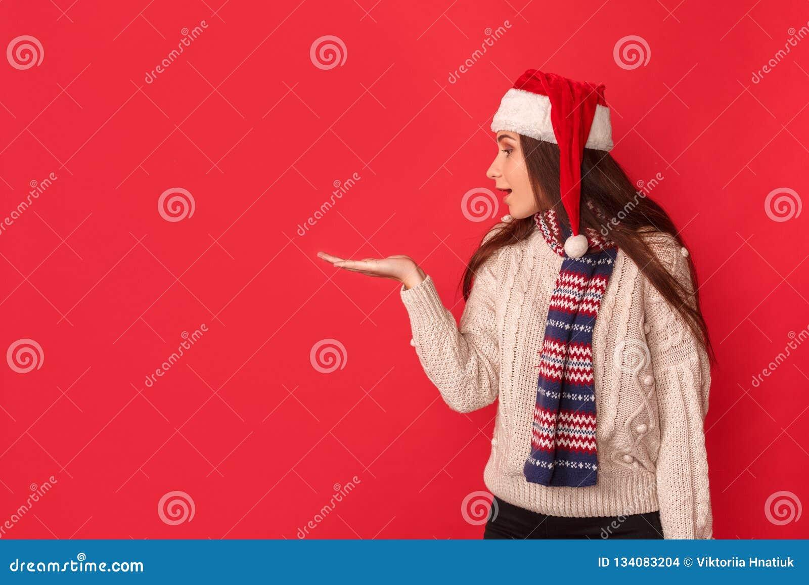 белизна торжества изолированная принципиальной схемой В сторону удивленная молодая женщина в положении шарфа и шляпы santa на кра