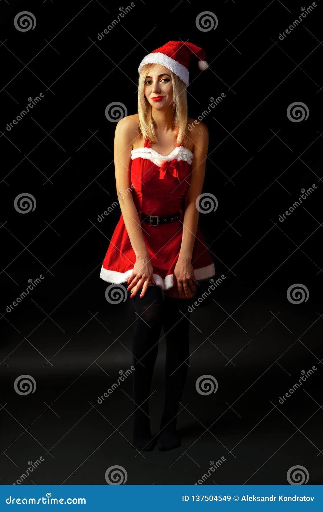 Белокурая девушка с ярким макияжем и красной губной помадой стоит в студии на темной предпосылке в сексуальном костюме Санта Клау