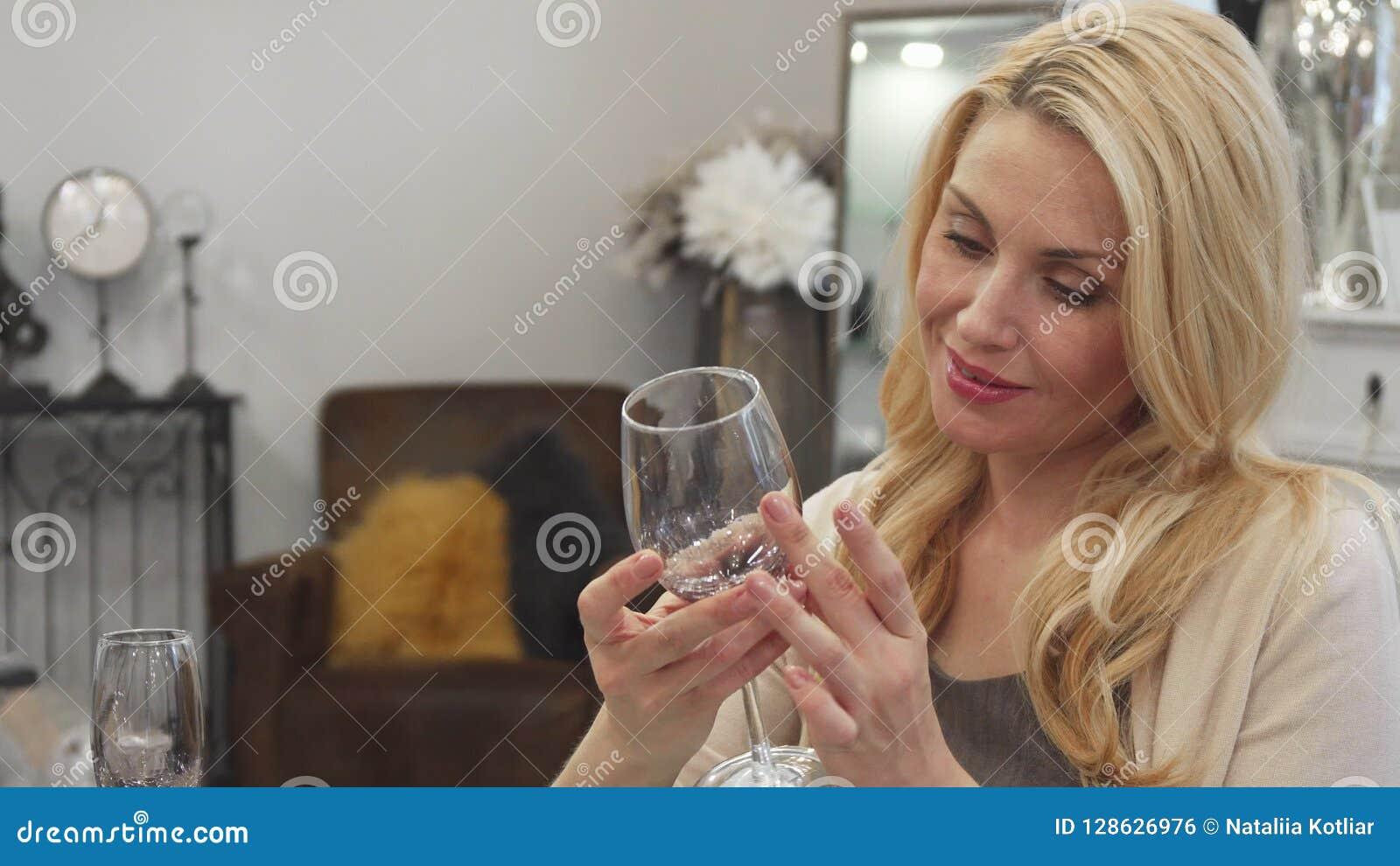 Белокурая женщина выбирает стекло для вина