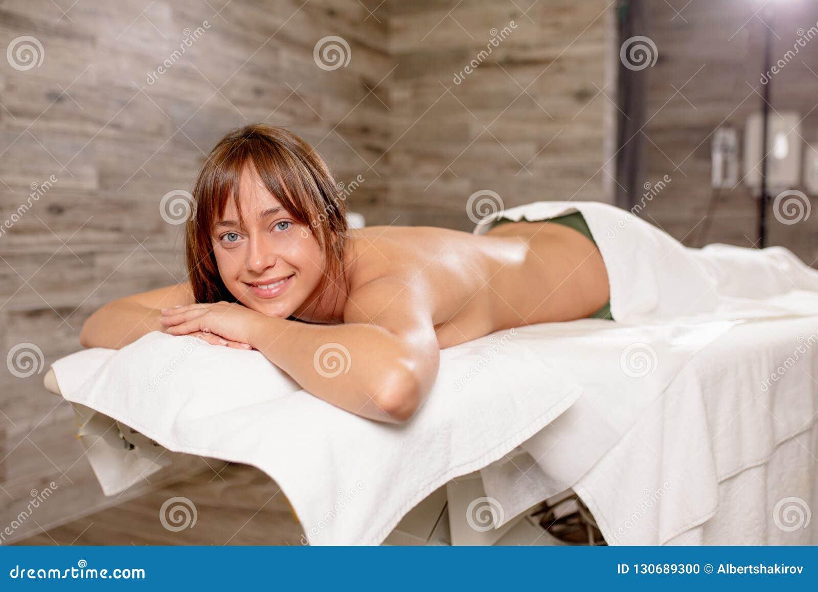 Белокурая женщина лежа на таблице массажа и смотря камеру
