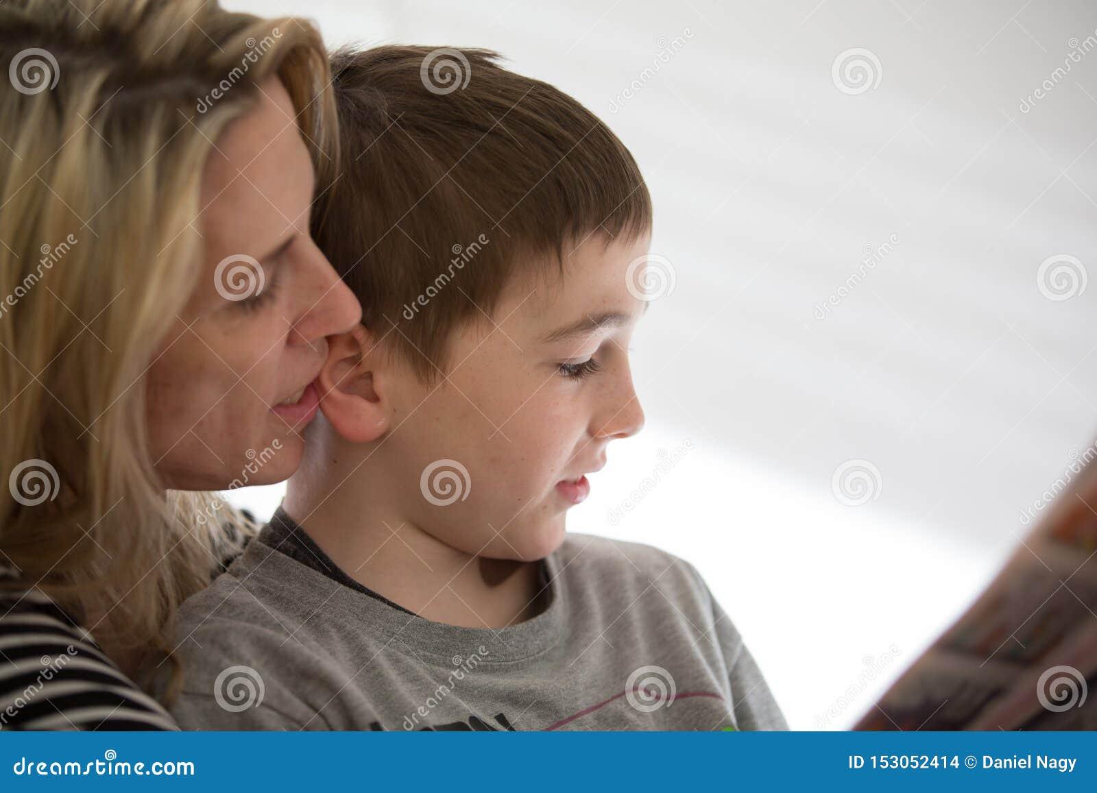 Белокурый мальчик матери и брюнета сидит совместно, и наслаждается чтением крытым r