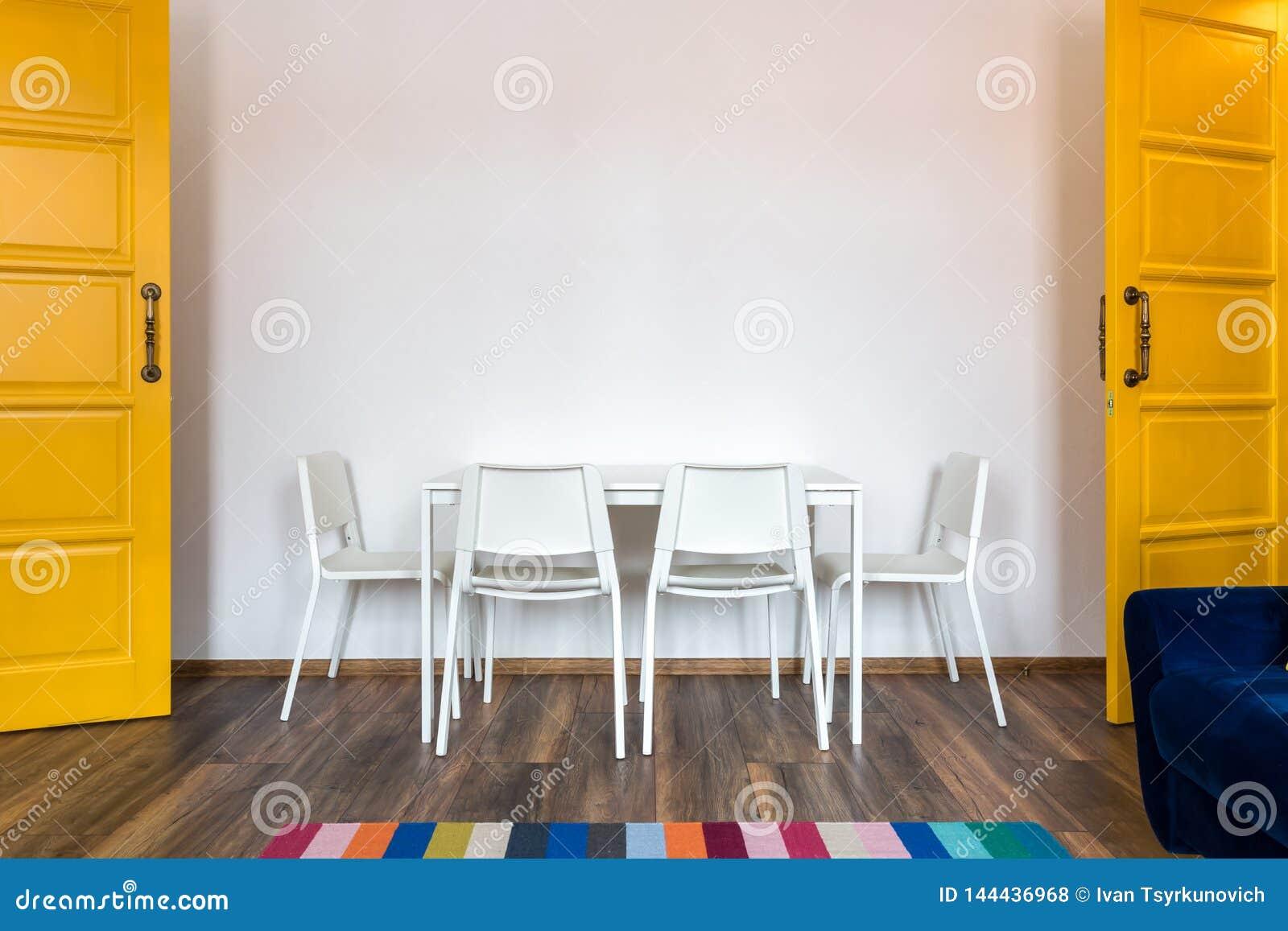 Белые деревянные стулья с таблицей на фоне белой стены в интерьере с желтыми дверями
